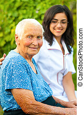 Smiling elderly woman with doctor outdoors - A young doctor...