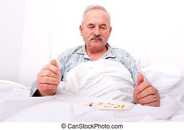 Elderly man eating meds - A senior man sitting in bed,...