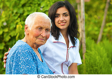 Outdoors with an elderly woman - A young doctornurse...