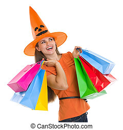 Happy woman in Halloween hat with shopping bags looking on...