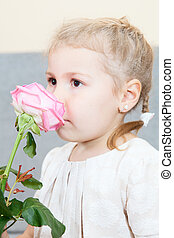 Young child smelling a pink rose flower