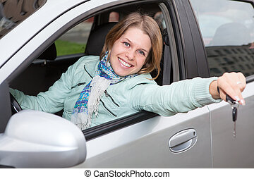 Happy smiling blond with ignition key showing in car window