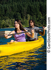 Lake Kayaking Couple - Couple paddling in kayak on lake.