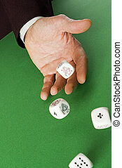 dice - Hand rolling dices on green table close up