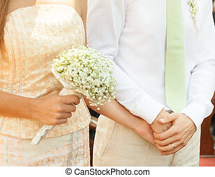 Marriage ceremony. - Close up of a bride and groom holding...