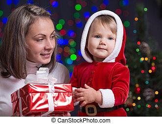 baby girl and her mother holding giftbox on bright festive background