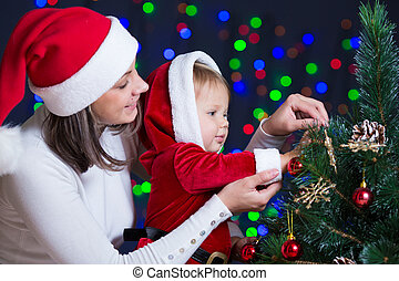 child girl with mother decorating Christmas tree on bright background