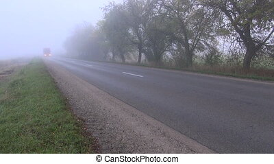 road with red truck and morning fog