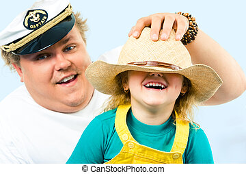 Playing - Photo of man putting hat on his daughter�s...