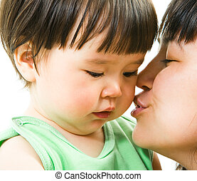 Sweet kiss - Close-up of mother kissing her small daughter...