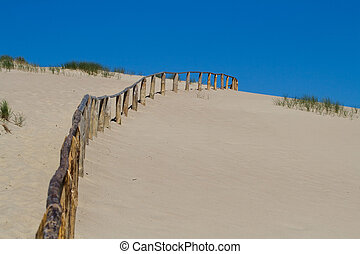 Fence in dunes - Wooden fence in sand dunes. Curonian Spit...