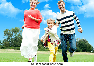 Catch me if you can - Active young parents running to catch...