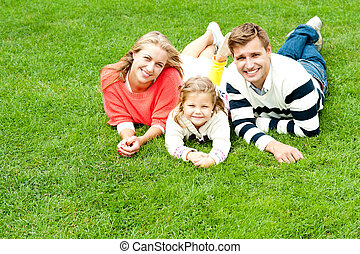 Laughing family of three having fun together on a sunny...