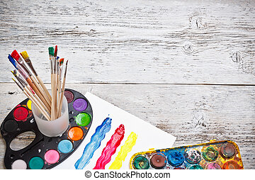 Box of watercolors and paintbrushes on wooden desk