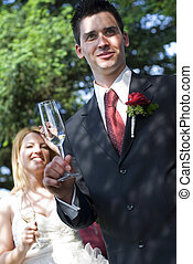 toast - young groom toasting with bride in background