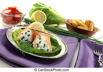 Salmon rolls with cream cheese and chives on a purple napkin