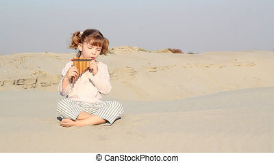 beautiful little girl play pan-pipe