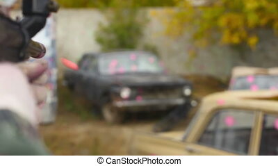 Paintball. - Shooting at the grunge car. Rack focus.