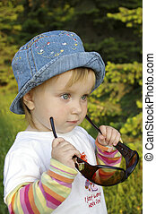 Little girl plays with glasses on nature - The little girl...