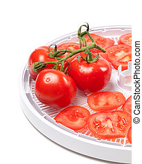 Ripe tomato on food dehydrator tray. Isolated on white...