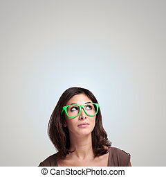 beautiful girl thinking with green eyeglasses on gray...