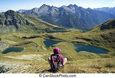 Girl admiring mountain lakes. Alps, Italy. Gran Paradiso...