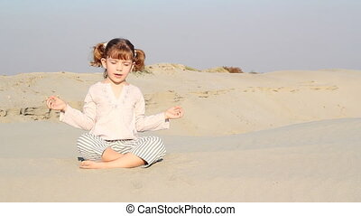 little girl meditating in desert