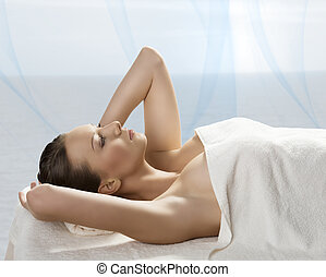 beautiful girl lying on a table with withe towel on her body...