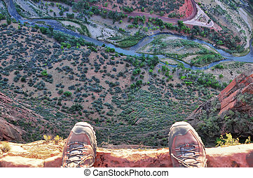 Feet on the edge of rock cliff high above the ground