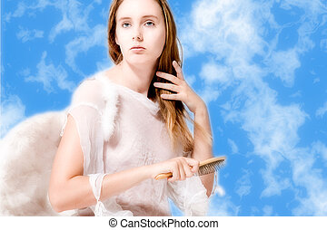 Beautiful angel in the clouds doing her hair - Portrait of...