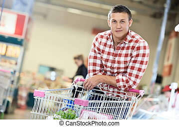 man at supermarket dairy shopping - man with shopping cart...