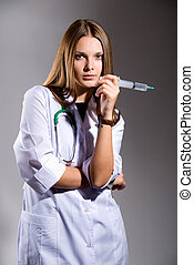 Female doctor with big syringe on grey background