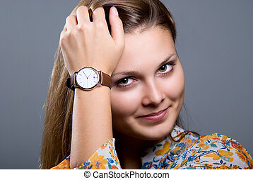 Beautiful girl with a wristwatch on gray background