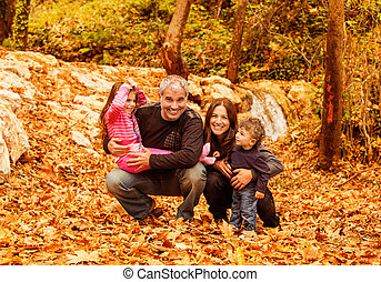 Cheerful family in autumn woods - Picture of cheerful young...