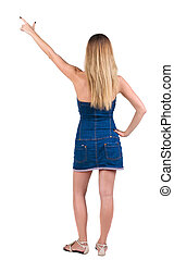 back of view beautiful young  woman in jeans dress pointing at wall. Rear view people collection.  backside view of person.  Isolated over white background.