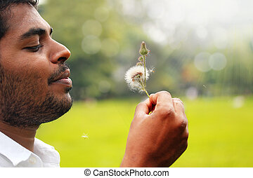 Close-up photo playful, free indian man blowing dandelion...