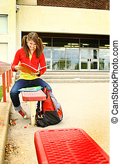 Revising - Young girl studying on a bench before class