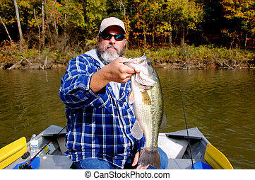 fisherman and bass - bearded fisherman holding large mouth...
