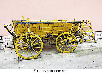 Old wagon - Old yellow wooden wagon standing in front of a...
