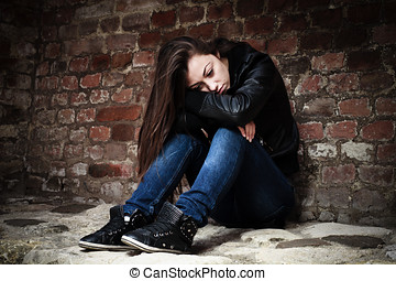 sad teenage girl - Sad teenage girl, leaning on an old brick...