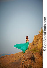 Beautiful girl standing on a precipice. Turquoise cape...