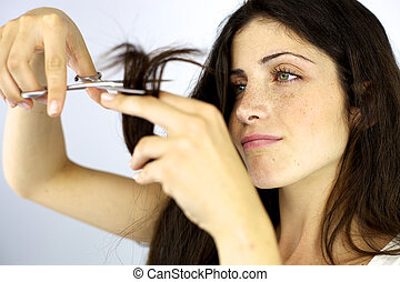 Serious beautiful woman cutting split ends hair