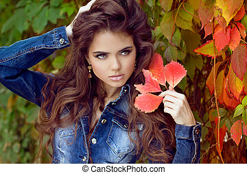 Autumn portrait of Beautiful Young woman posing at park