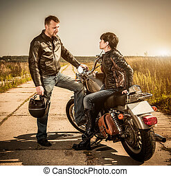 Bikers - Biker man and girl sits on a bike