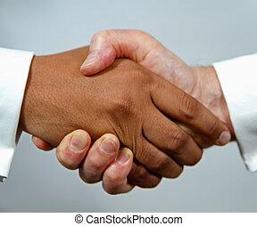 Interracial handshake - Handshake between smartly dressed...