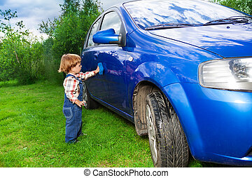 adorable child helping to wash car - little child washing...