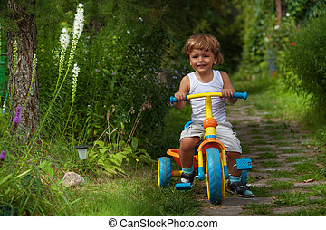 little boy riding tricycle - cute child riding his trike in...