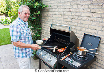 Retired dutch senior man grilling meat in his back yard on a...