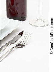 Place setting with white plates and red wine on white cloth