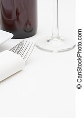 Place setting with  plates and red wine on white cloth